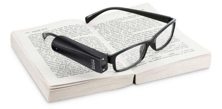 OrCam MyEye 2 mounted on a pair of glasses resing on an open book