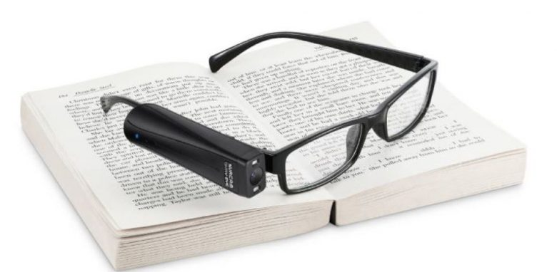 OrCam MyEye 2 attached to a pair of glasses placed on a book.